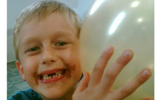 Mucky faced boy with balloon